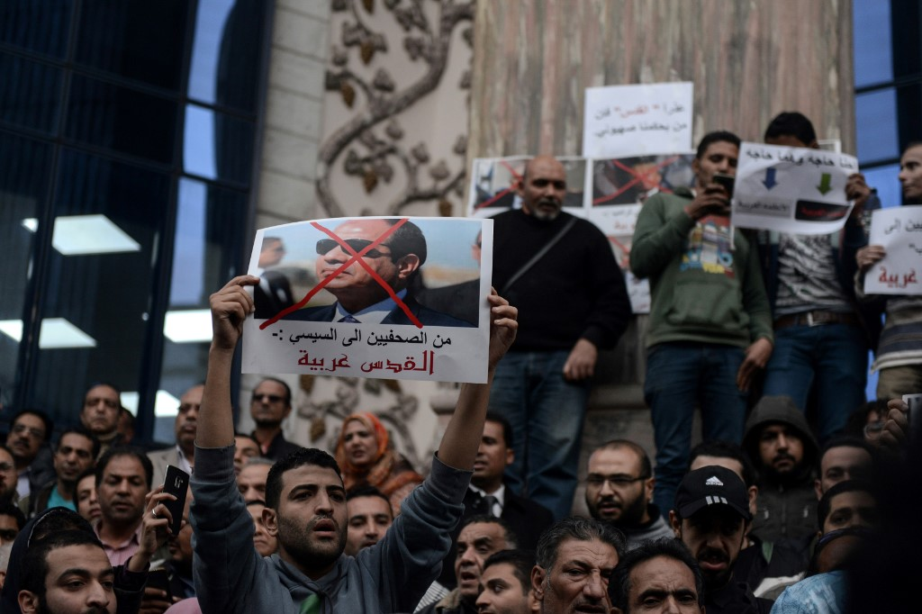 Egyptian protesters hold up a portrait of Sisi in Cairo on 7 December 2017 (AFP)