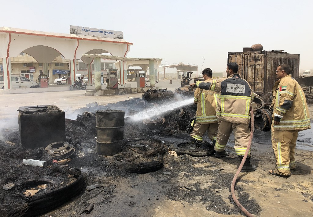 Firefighters extinguish a fire following clashes in Aden's Mansoura district on Sunday (AFP)