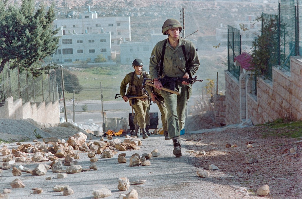 Israeli soldiers patrol Nablus amid demonstrations during the First Intifada in 1987 (AFP)
