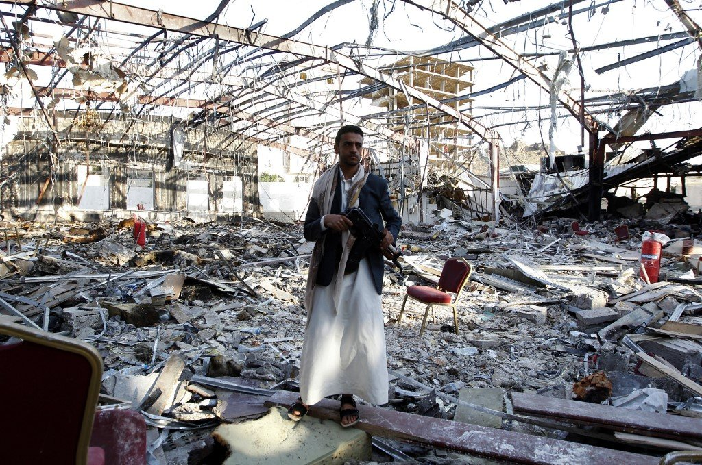 A Yemeni man stands where the Al-Kubra hall, bombed by the Saudi-led coalition in October 2016, once stood (AFP)