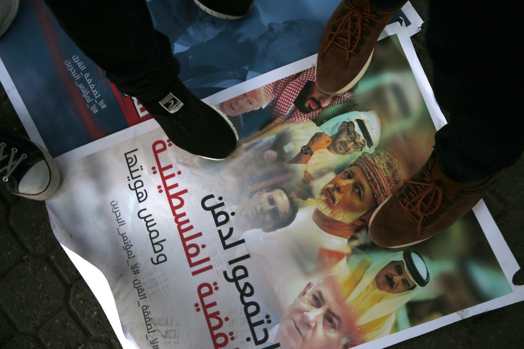 Palestinians step on a placard displaying pictures of Gulf, Israeli and US leaders during a protest in Gaza City in June 2019 (AFP)