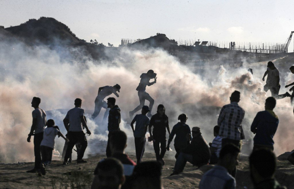 Palestinian protesters run from tear gas canisters fired by Israeli forces in Gaza on 1 November (AFP)