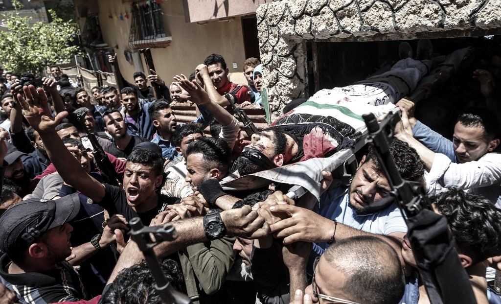 Mourners carry the body of a 22-year-old Palestinian killed during a protest in the Gaza Strip on 4 May (AFP)