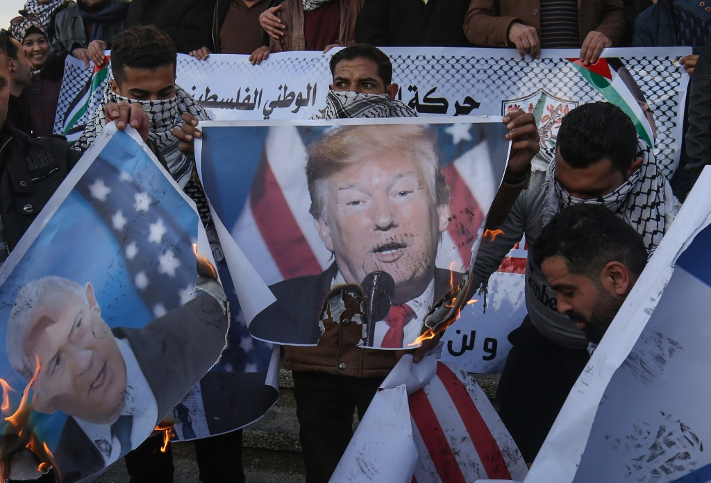Palestinian demonstrators burn images of US President Donald Trump and Israeli Prime Minister Benjamin Netanyahu in Rafah, Gaza, on 29 January (AFP)