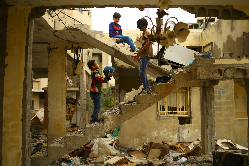 Palestinian children play amid the ruins of a building destroyed during the 2014 Israeli assault on Gaza (AFP)