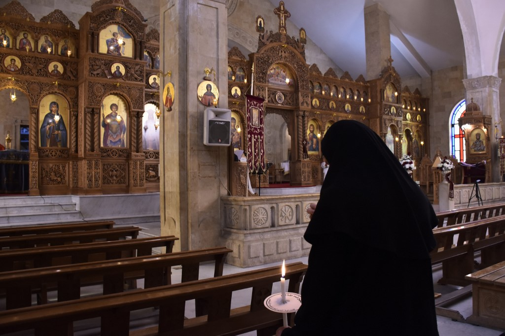 A nun attends mass at a Greek Orthodox church in Aleppo, Syria, on 19 April (AFP)