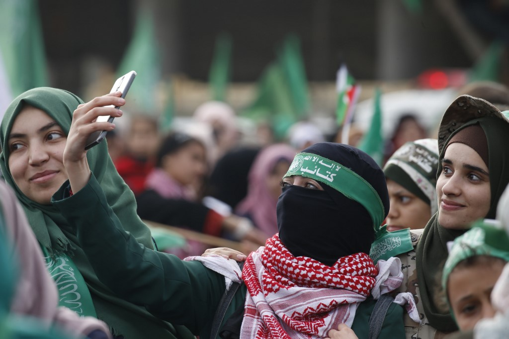 A woman takes a selfie as Palestinians attend a rally marking the 31st anniversary of Hamas' founding, in Gaza City on 16 December 2018 (AFP)