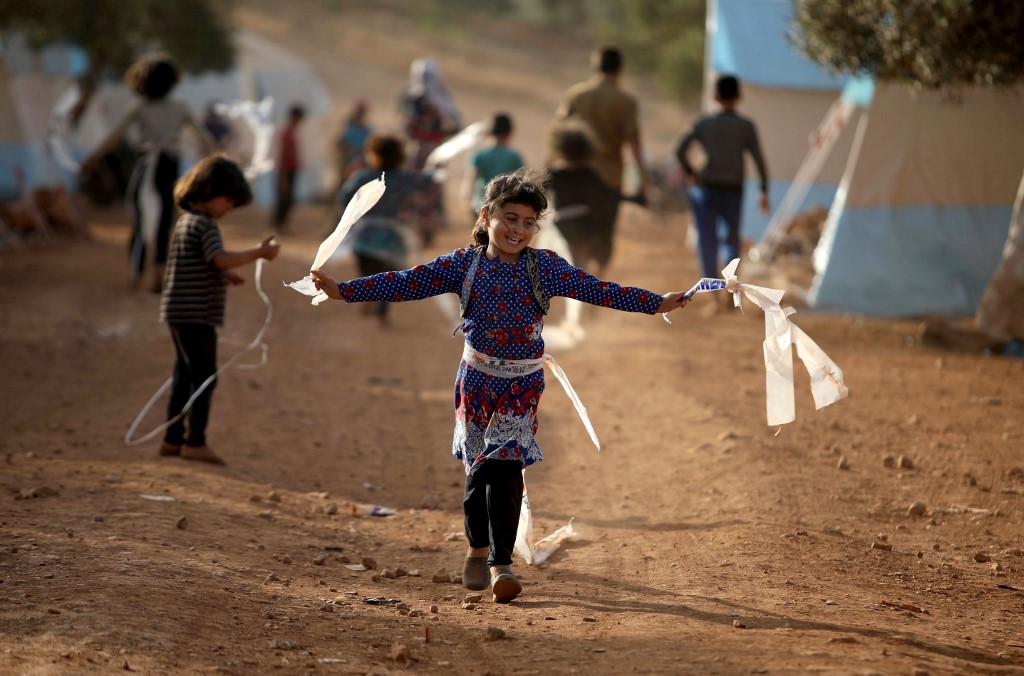 Syrian children play in a camp for displaced people near the Turkish border on 3 June (AFP)