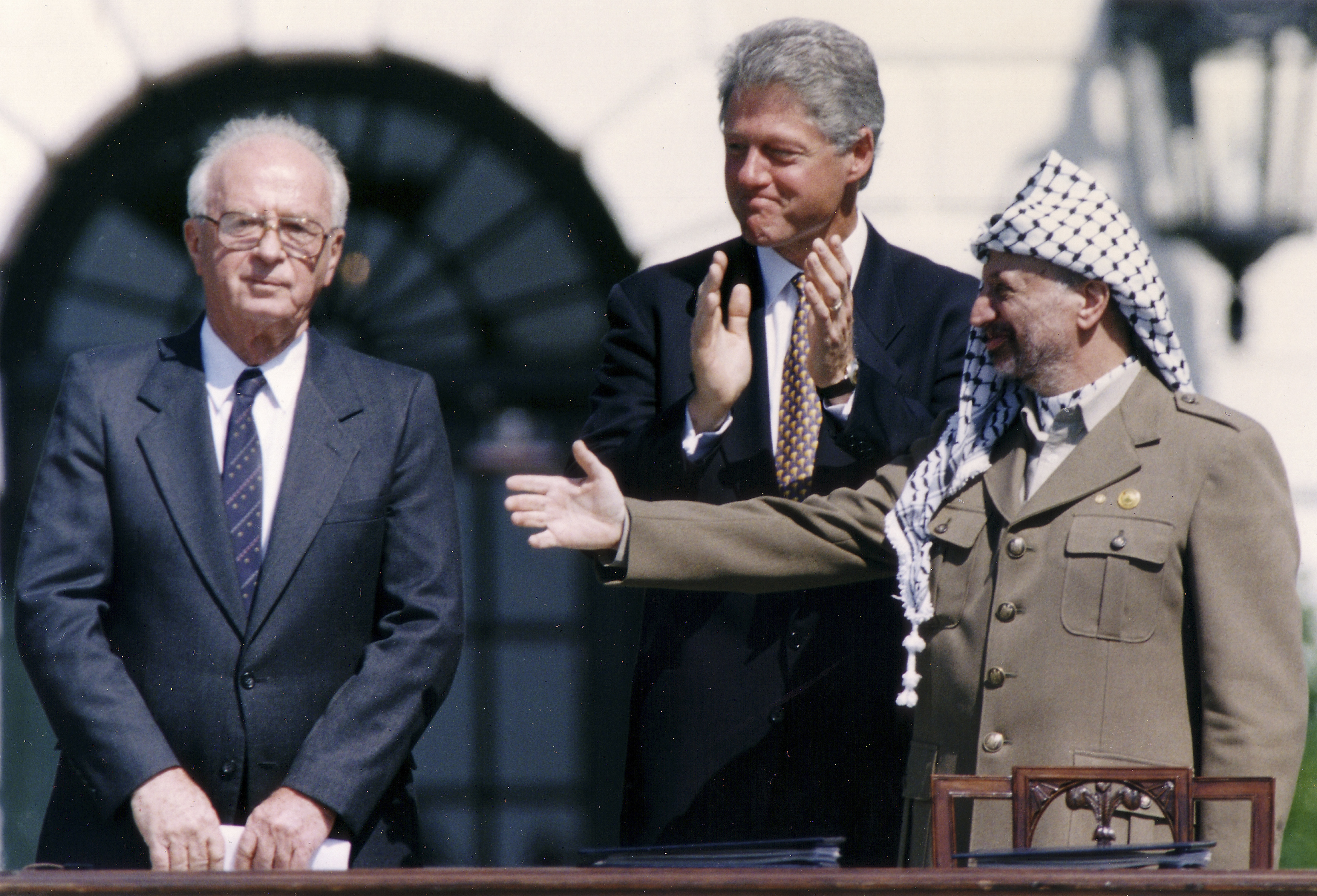 US President Bill Clinton stands between PLO leader Yasser Arafat and Israeli Prime Minister Yitzhak Rabin as they shake hands in September 1993 in Washington after signing the first Oslo accord (AFP)