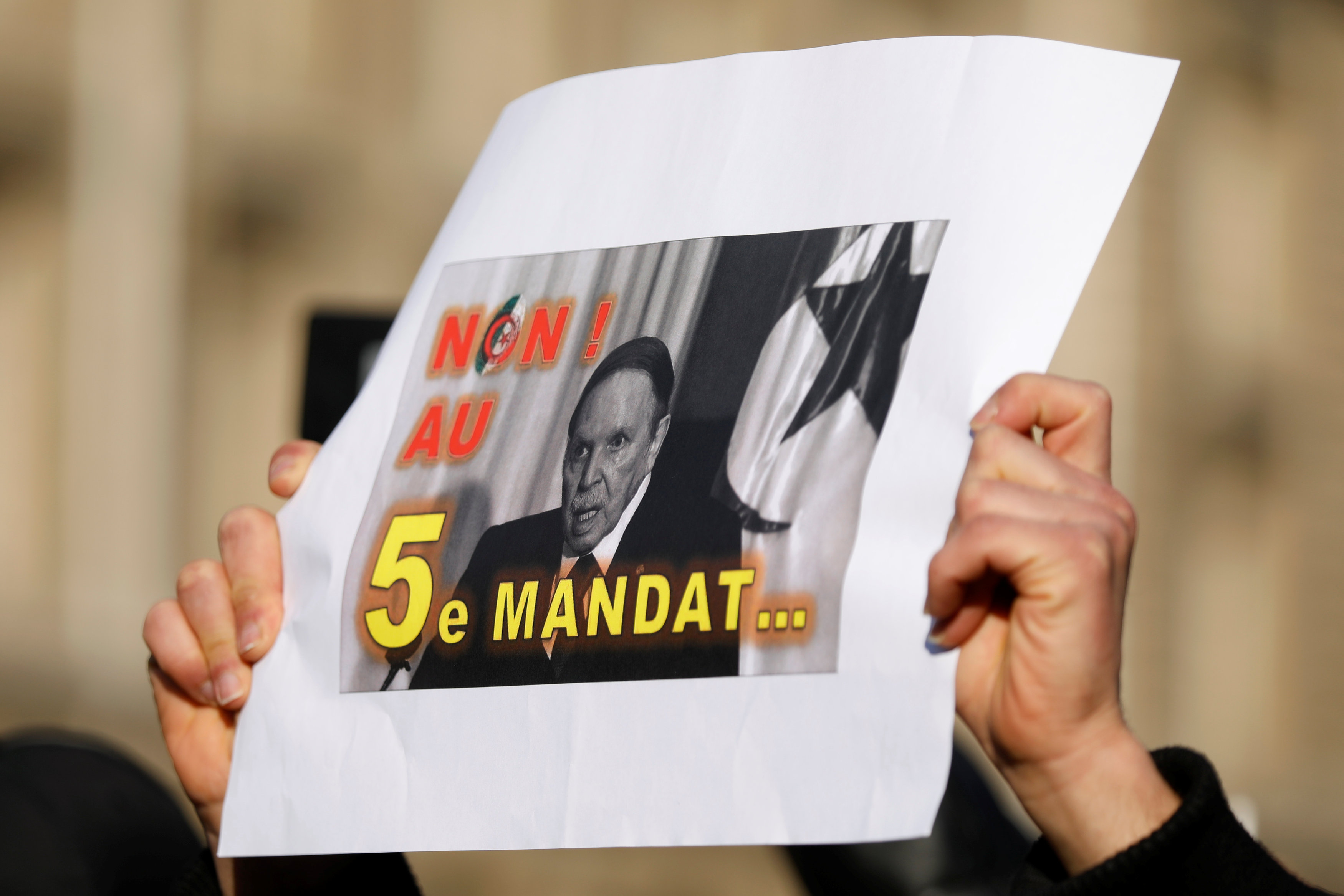 A demonstrator holds up a placard during a protest against President Abdelaziz Bouteflika seeking a fifth term (Reuters)