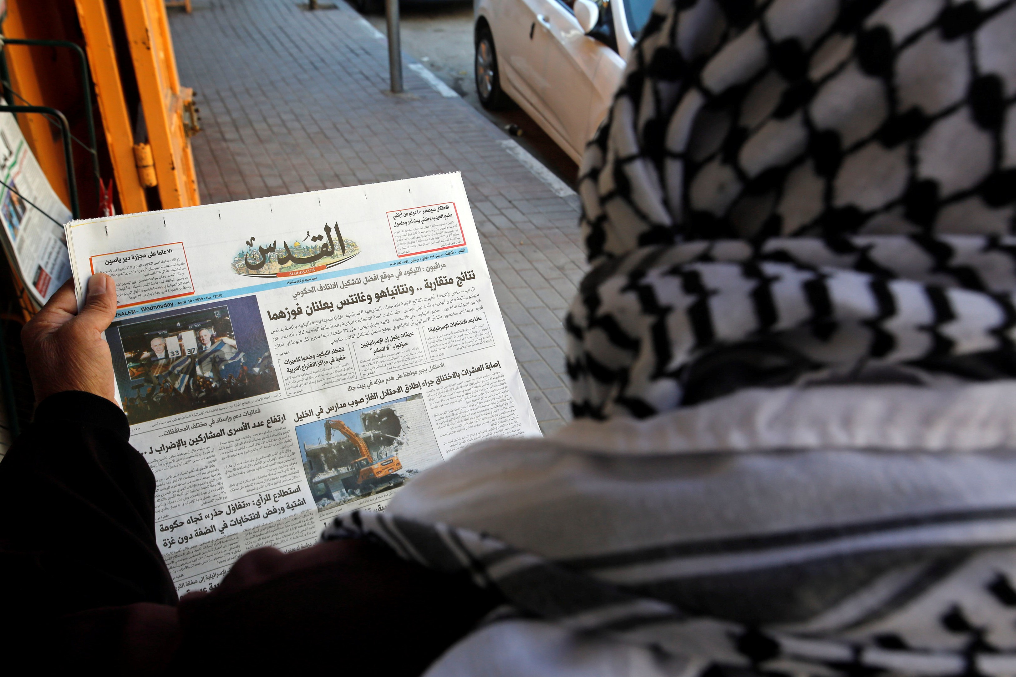 A Palestinian man reads a local newspaper with news of the Israeli election, in Hebron, in the Israeli-occupied West Bank on 10 April (REUTERS)