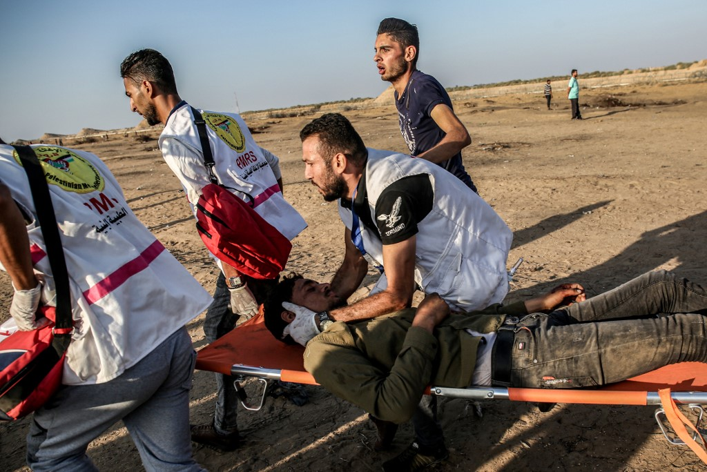 Palestinian paramedics carry an injured protester in Gaza on 27 September (AFP)