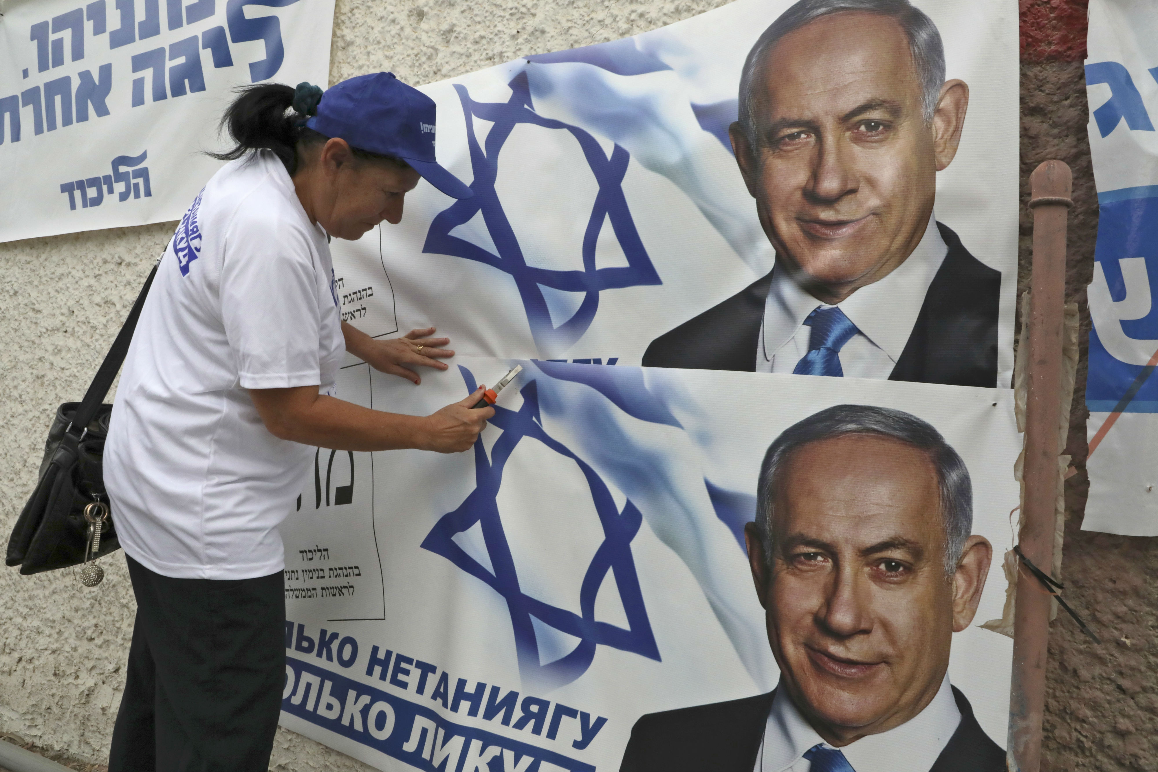 A woman places electoral banners for the Likud party showing chairman and Israeli Prime Minister Benjamin Netanyahu in the southern Israeli city of Beersheva (AFP)