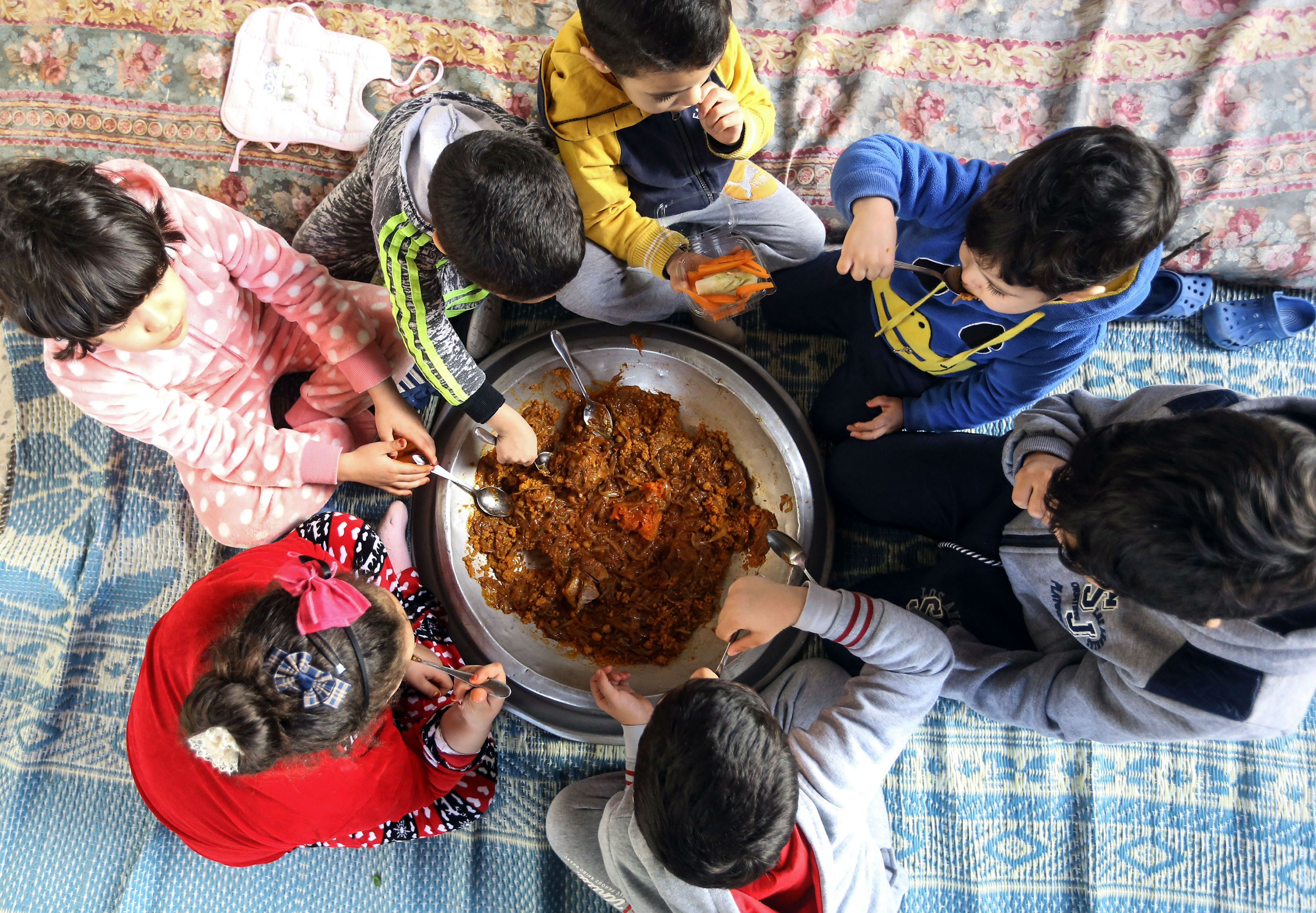 Libyan children preparing to eat freshly cooked couscous with lamb and onions in Tripoli in February 2018 (AFP)