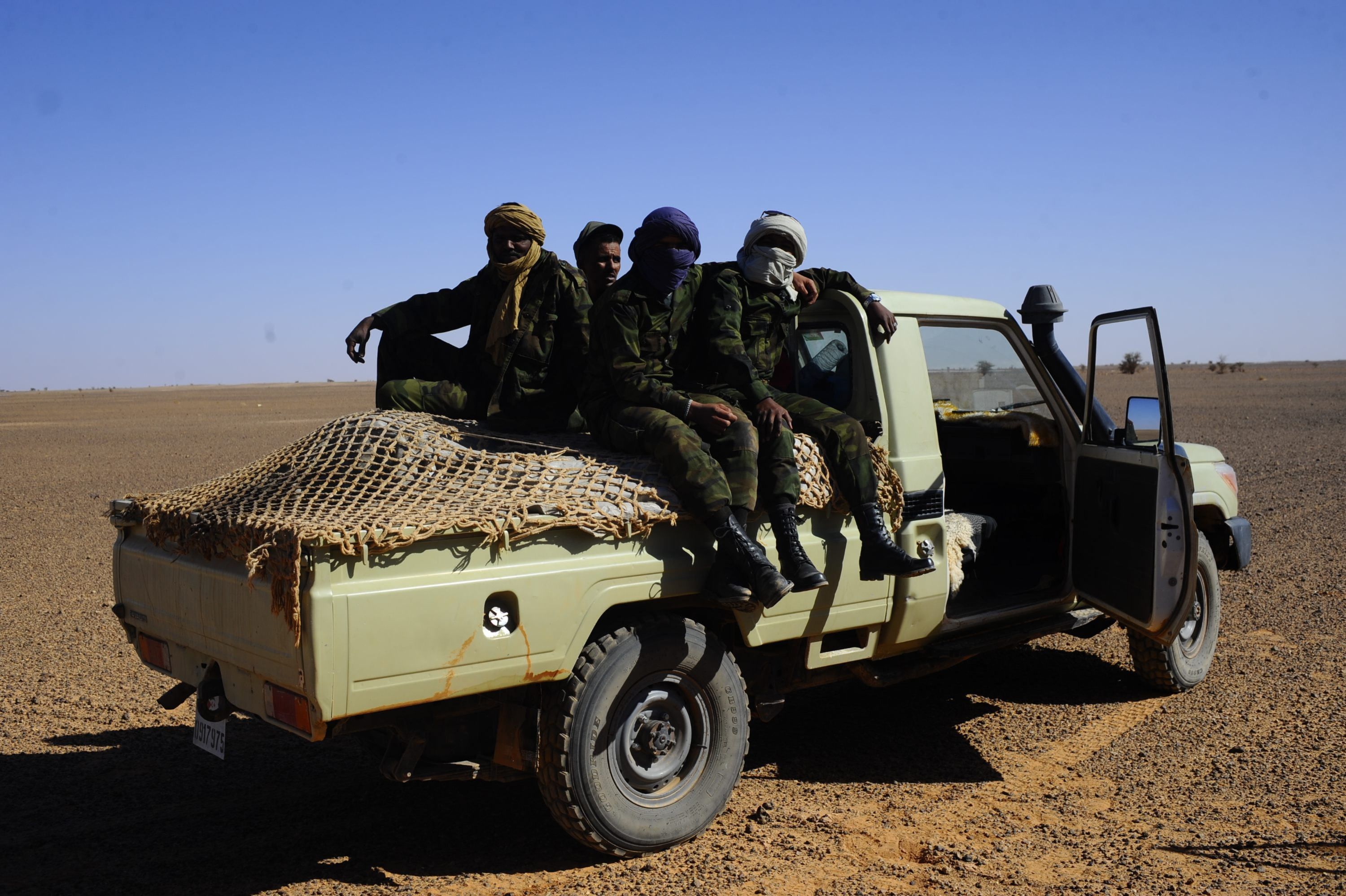 Members of the Polisario sit on a pick-up truck in the Western Sahara in 2014 (MEE/Oscar Rickett)