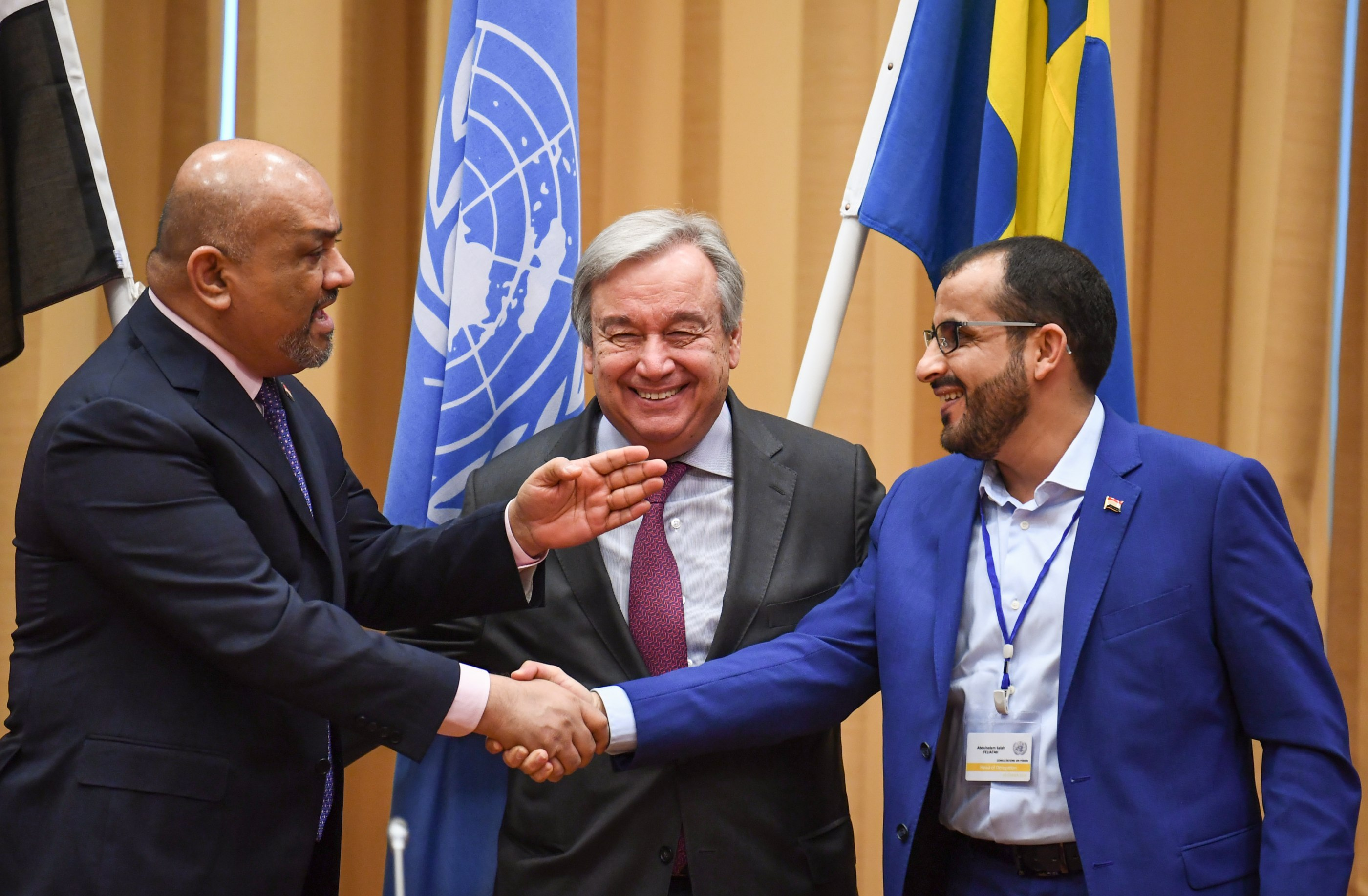 Yemeni government Foreign Minister Khaled al-Yamani, left, and the head rebel negotiator Mohammed Abdelsalam, right, shake hands under the eyes of United Nations Secretary-General Antonio Guterres, centre, during peace consultations taking place at Johannesberg Castle in Rimbo, north of Stockholm, Sweden, on 13 December 2018 (AFP)