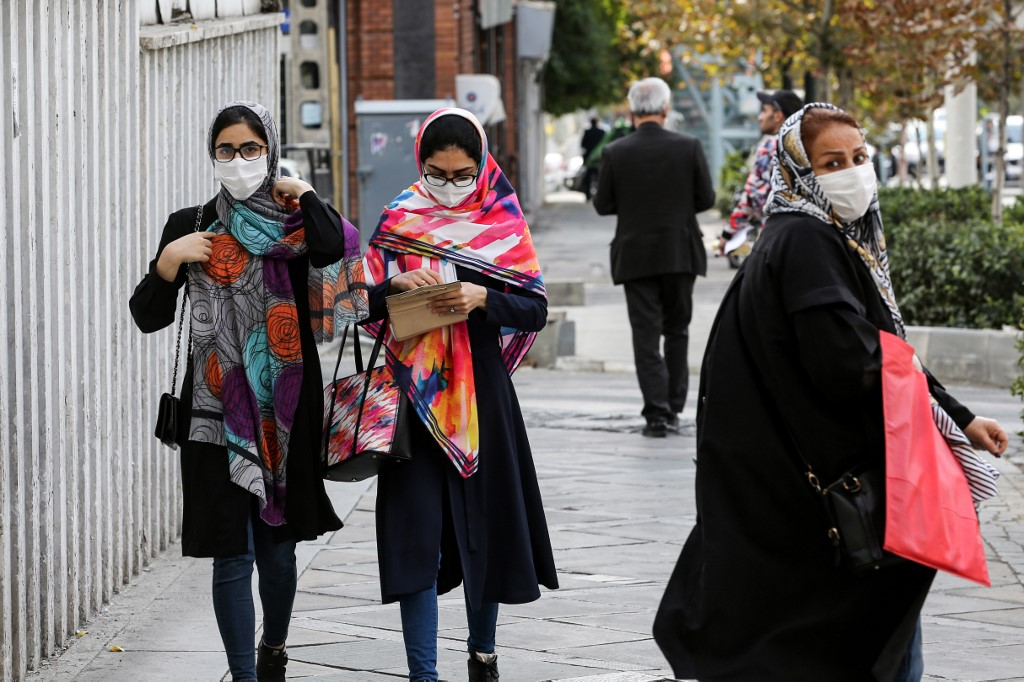 Women, mask-clad due to the COVID-19 coronavirus pandemic, walk along a street in Iran's capital Tehran on November 8, 2020.