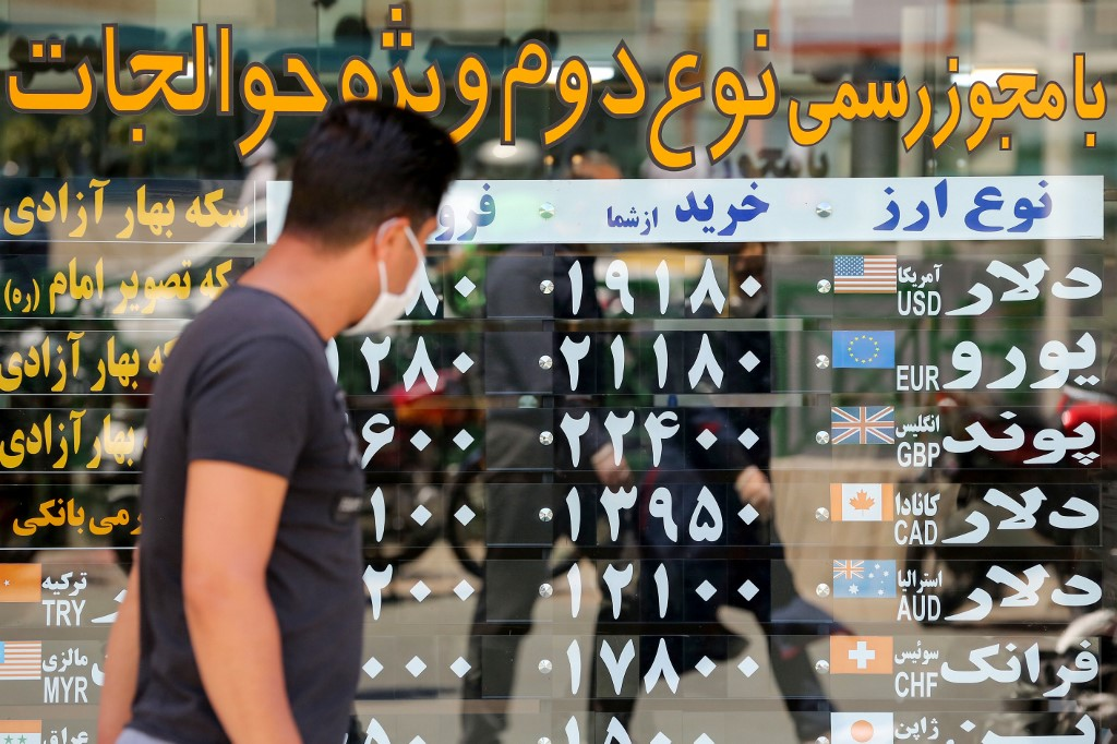 A man, wearing a protective mask due to the COVID-19 coronavirus, checks the currency exchange rates as he walks in the Iranian capital Tehran on June 22, 2020.  ATTA KENARE / AFP