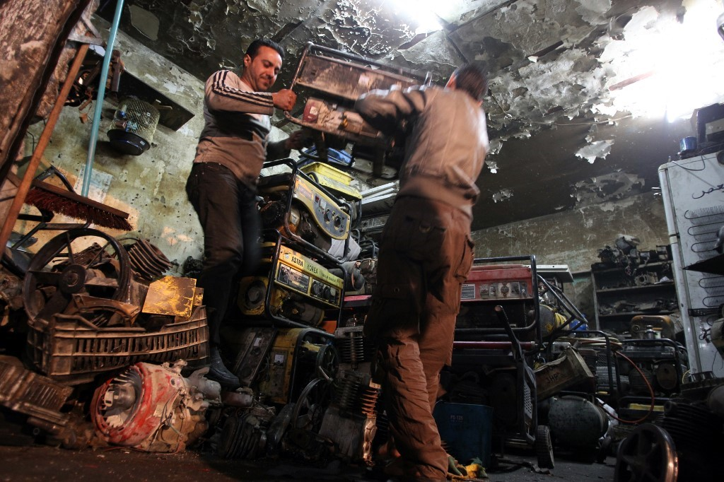 Iraqi men carry a diesel generator, which are often bought by individuals to supply electricity to their homes due to frequent power cuts, at their shop in the capital Baghdad on March 19, 2014.