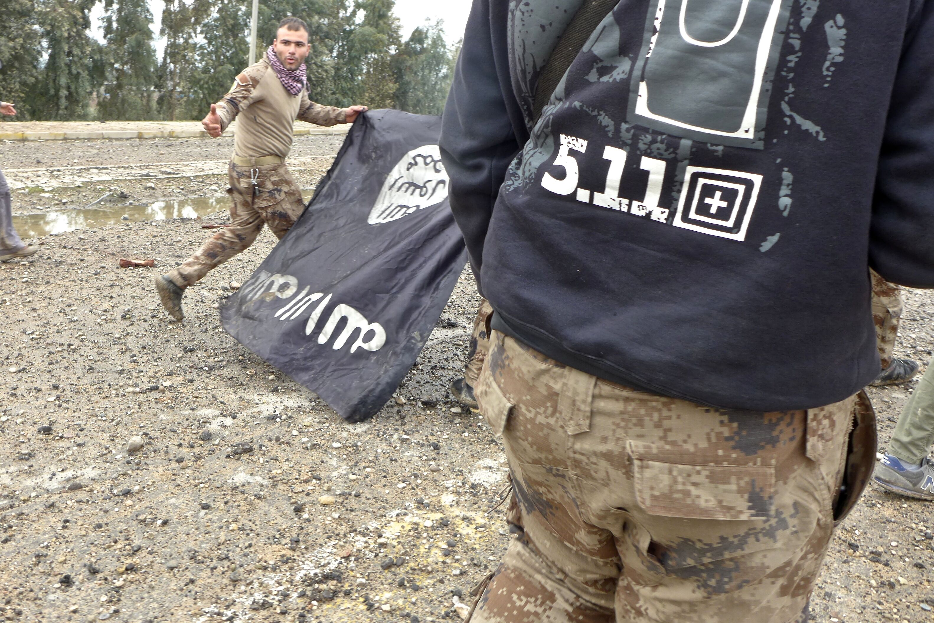 Iraqi Special Forces pull down an IS flag in Mosul in 2017 (MEE/TomWestcott)