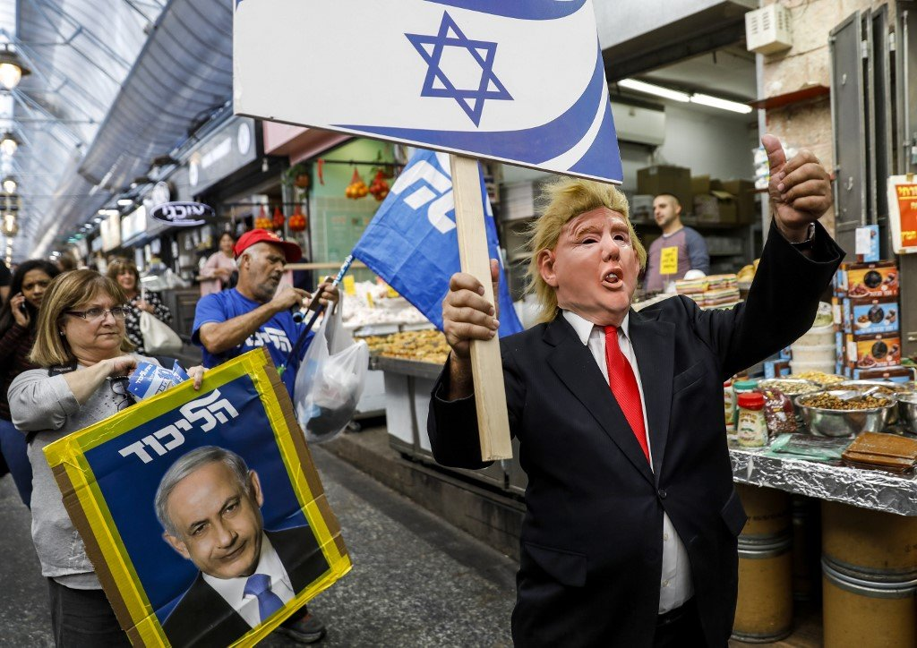 A supporter of Israeli Prime Minister Benjamin Netanyahu wears a mask portraying Trump's face in Jerusalem on 7 April (AFP)