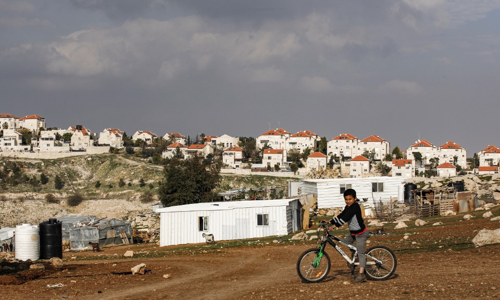 A boy rides a bicycle past Palestinian Bedouin huts in the occupied West Bank on 28 January, with the Israeli settlement of Maale Adumim in the background (AFP)