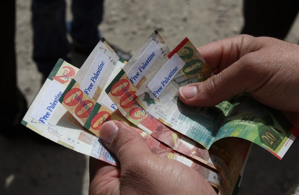 Israeli shekels are seen marked with 'Free Palestine' stickers in 2011 (AFP)