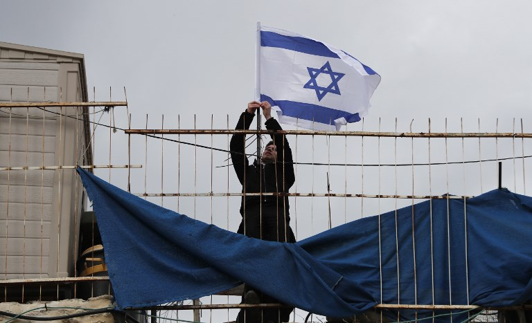 Settlers place an Israeli flag atop a Palestinian home in Jerusalem on 17 February (AFP)