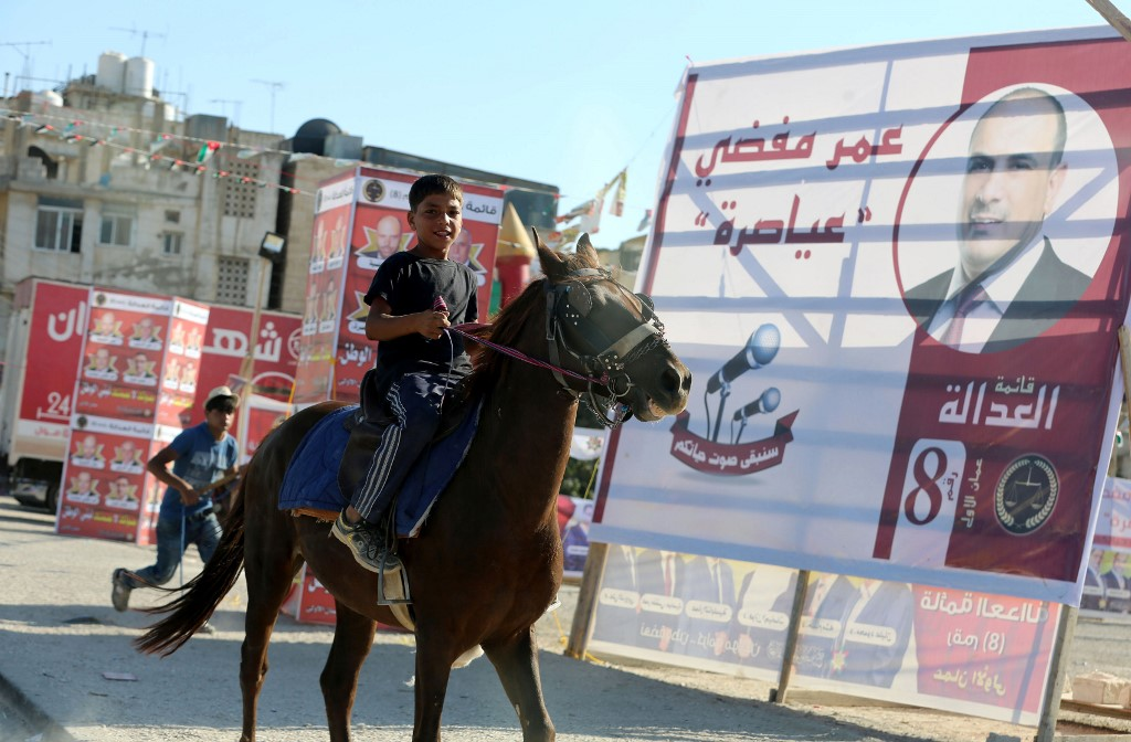 A boy rides a horse past election campaign posters in Amman in 2016 (AFP)