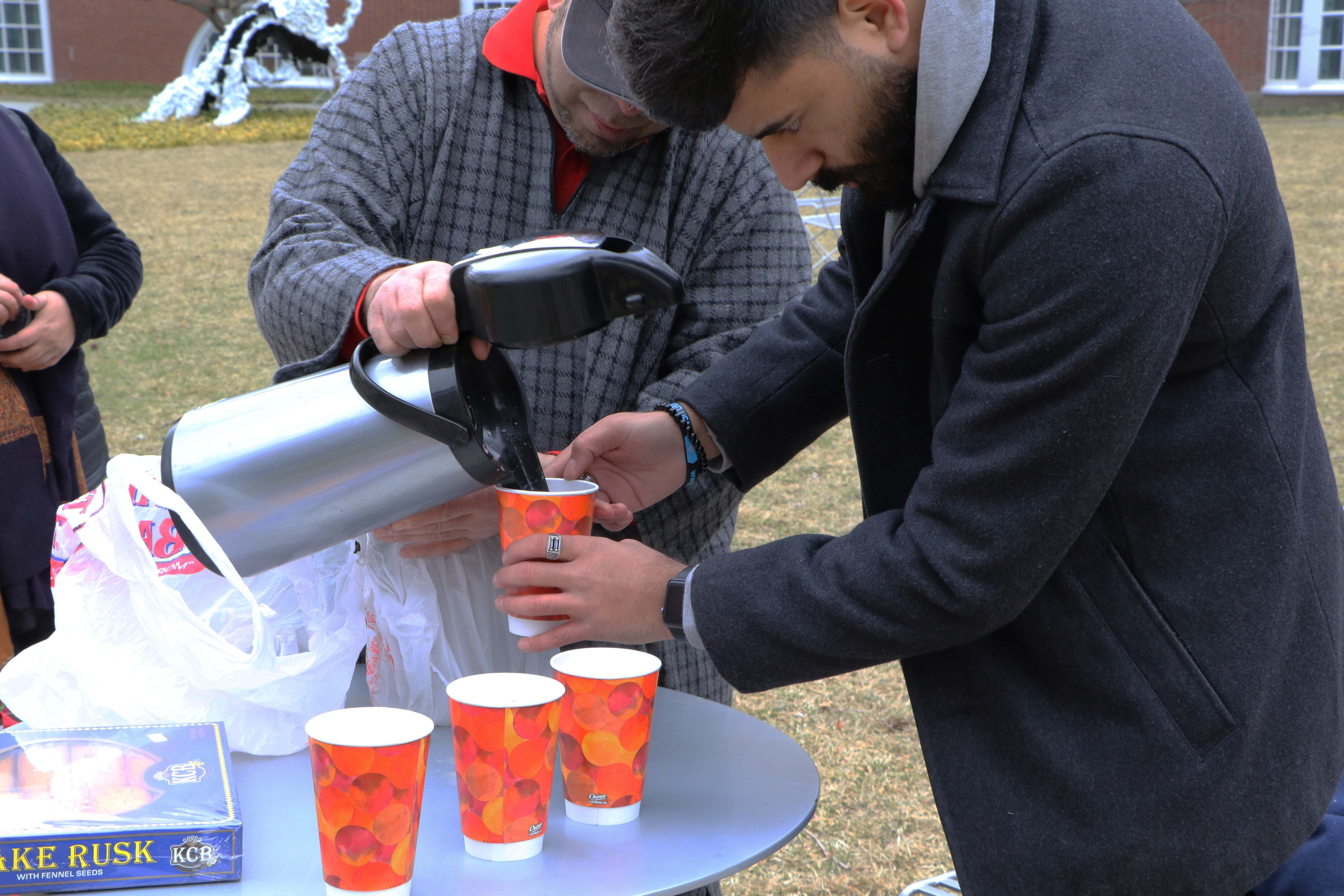 A man pours in tea into paper cups.