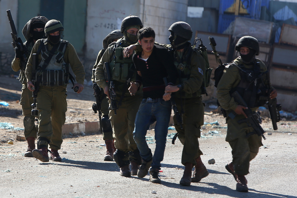 A Palestinian youth was arrested by Israeli police in Qabatiya on 4 February, 2016 (AFP)