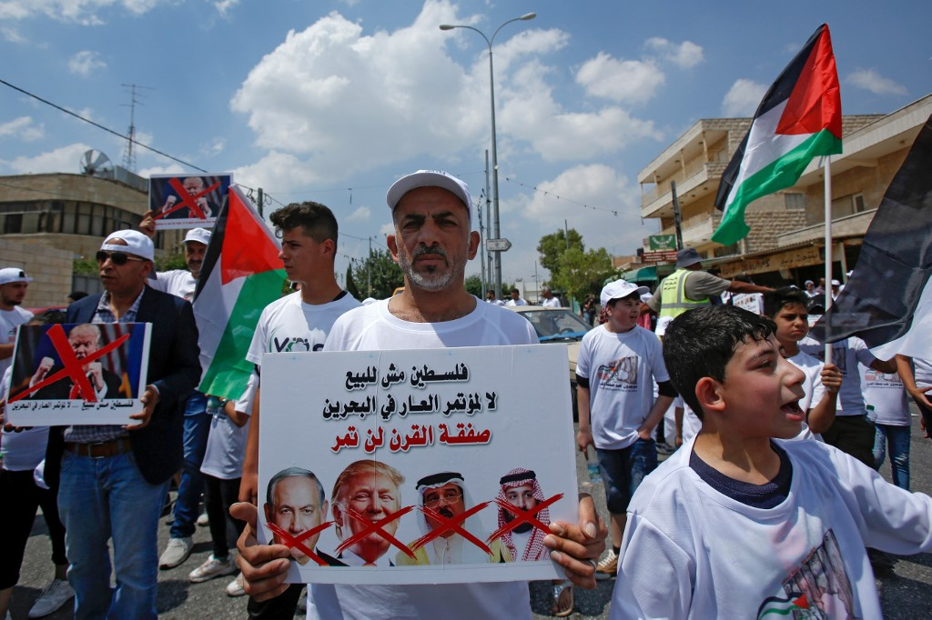 A Palestinian man holds up a sign criticising Israeli, US, Bahraini and Saudi leaders over the forthcoming Manama conference on 16 June in Bethlehem (AFP)