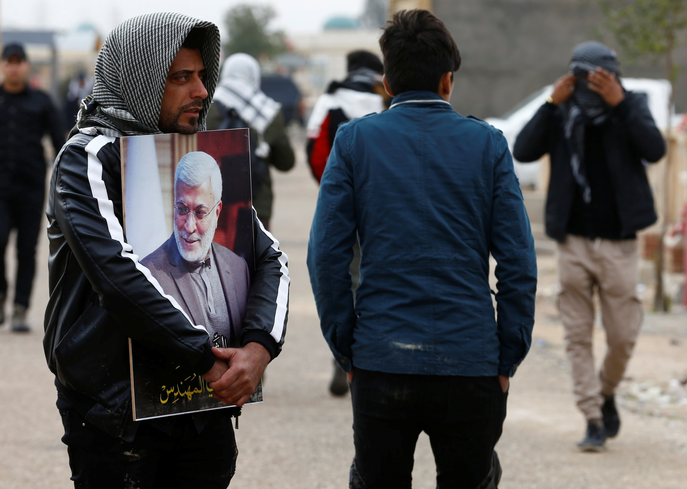 Mourners attend the burial of Iraqi militia commander Abu Mahdi al-Muhandis in Najaf on Wednesday (AFP)