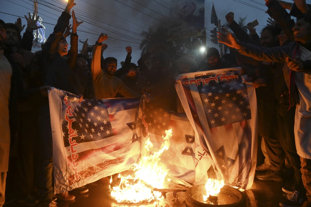 Protesters in Lahore, Pakistan, burn US and Israeli flags after the US assassination of Iranian commander Qassem Soleimani on 7 January (AFP)