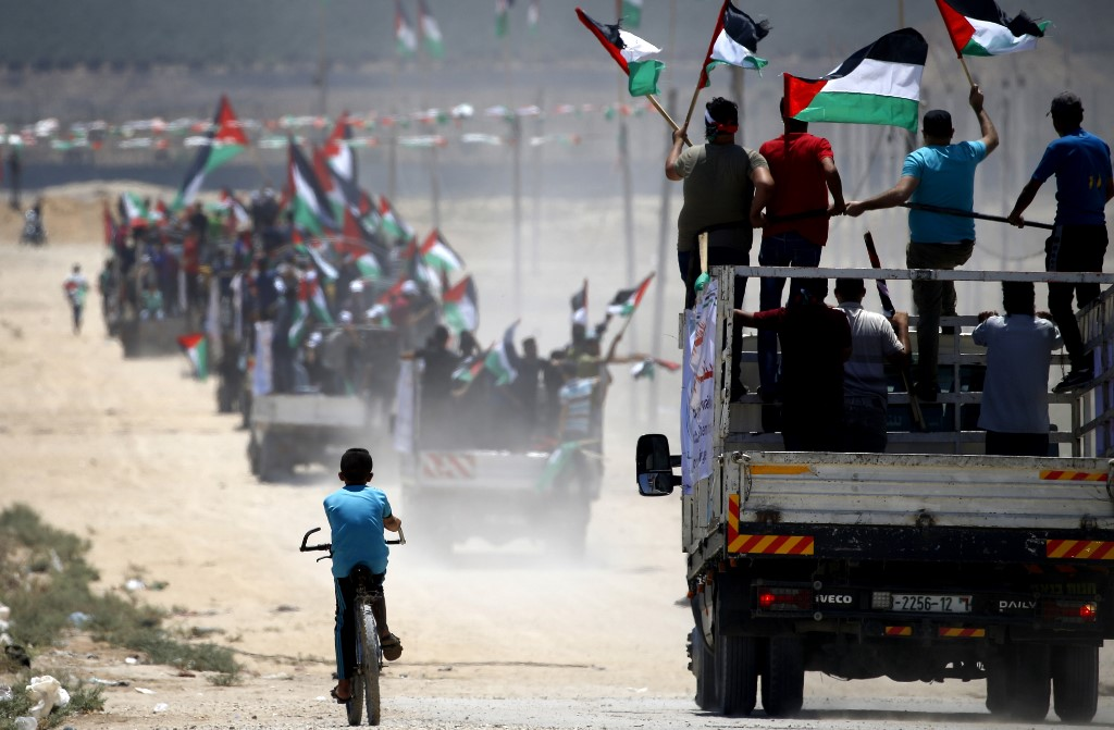 Palestinian demonstrators drive towards the Israel-Gaza fence on 22 July (AFP)