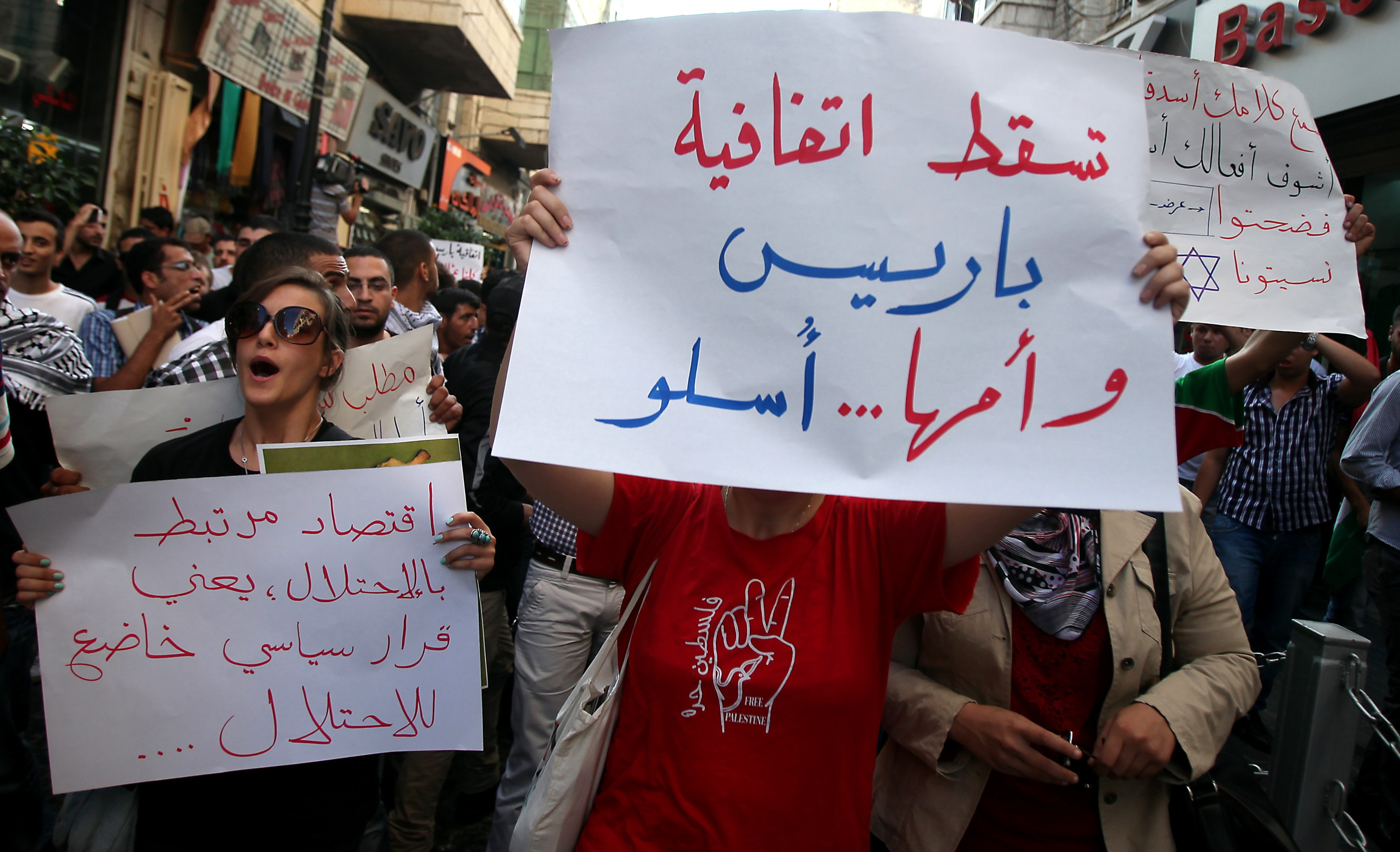 "A Palestinian protester holds a placard that read in Arabic ""Down with the Paris Protocol and the Oslo Agreement"" during a protest against both key accords, which govern economic ties between Palestinians and Israelis, in the West Bank city of Ramallah in 2012 (AFP)"