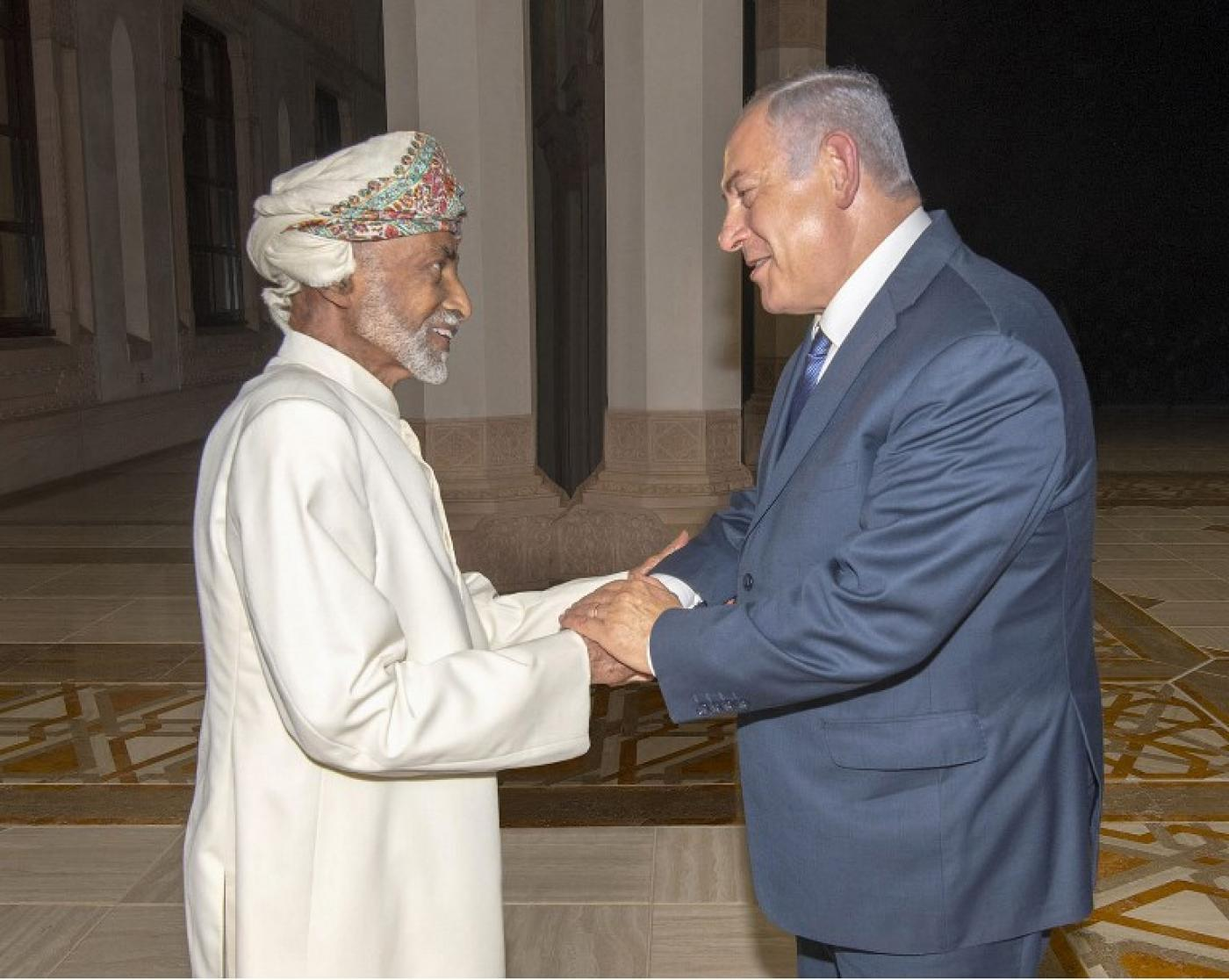 A handout picture released by the Omani Royal Palace shows Oman's Sultan Qaboos, left, with Israeli Prime Minister Benjamin Netanyahu in Muscat on 26 October (AFP)