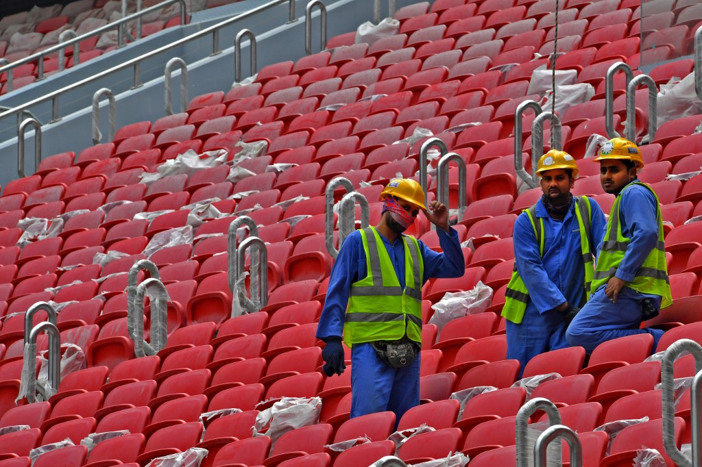 Construction workers are seen on 17 December at Qatar's new al-Bayt Stadium, which will host matches of the World Cup in 2022 (AFP)
