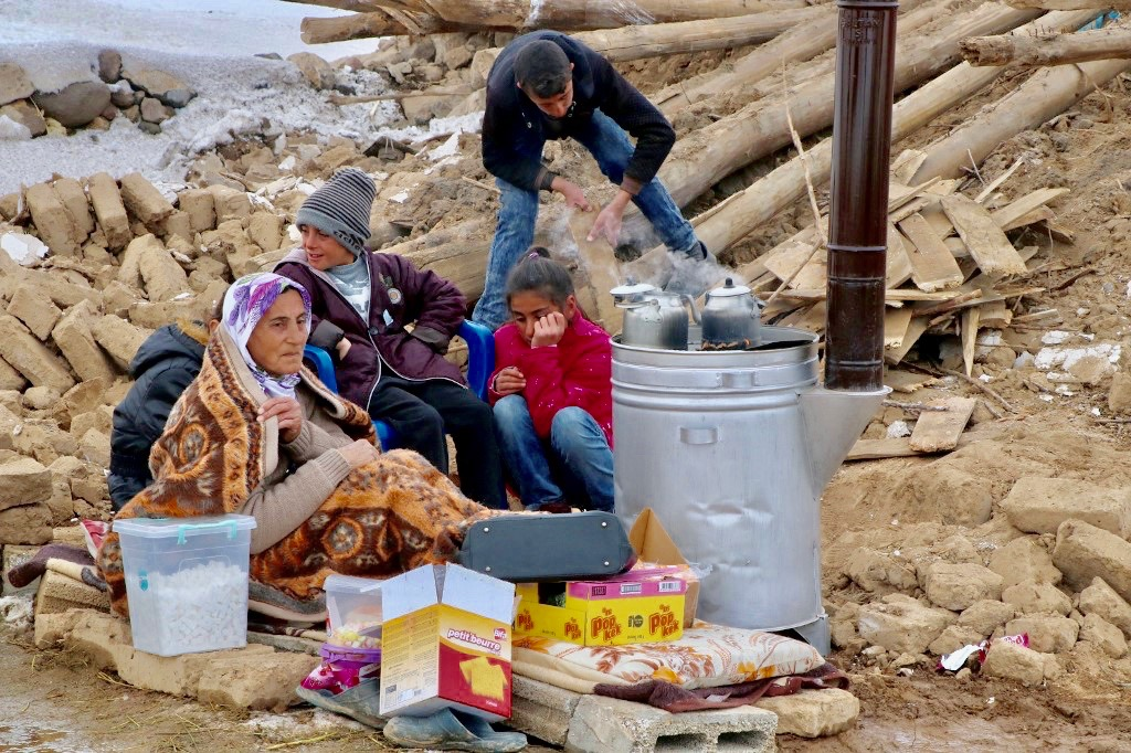 People gather around stove in Baskale, in Turkey's Van province, after earthquake on Sunday (AFP)