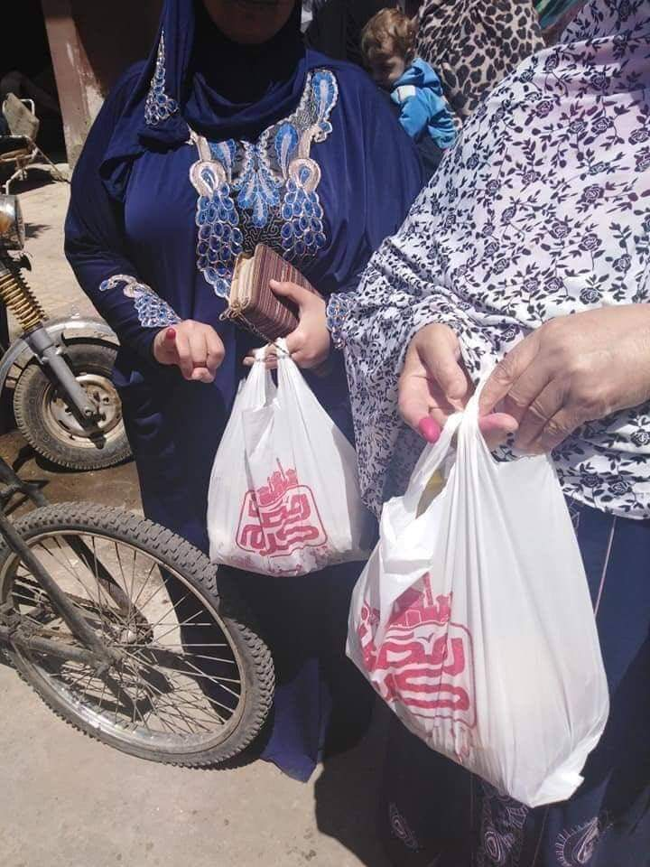 Egyptian women carry their food parcels after voting in the referendum in Cairo (MEE)