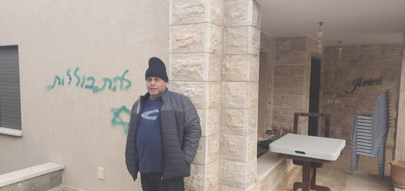 A resident of Jish village stands next to a slogan sprayed by Israeli settlers saying 'Stop assimilating' (Arab48 news)