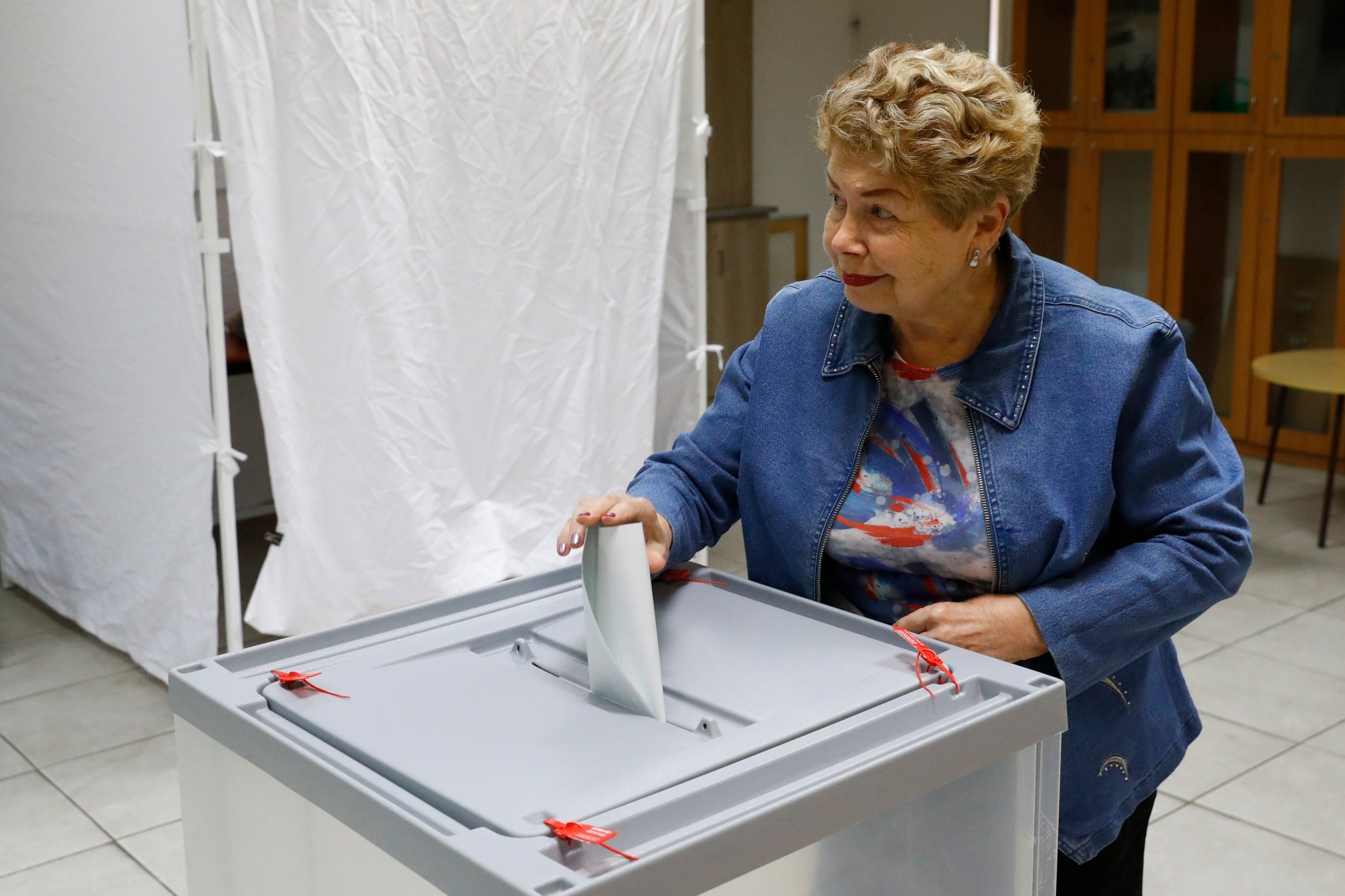 A Russian national residing in Israel casts her vote at a polling station in the coastal city of Netanya, during Russia's 2018 presidential election (AFP)