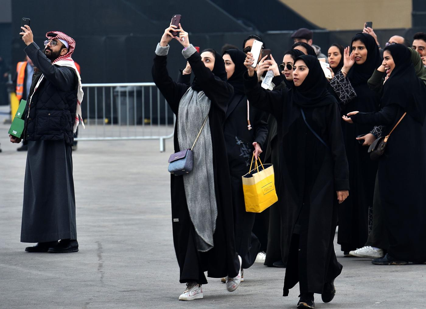 Saudi women take photographs with their mobile phones prior to Saudia Ad Diriyah E-Prix Formula E Championship in Riyadh, on 15 December, 2018 (AFP)