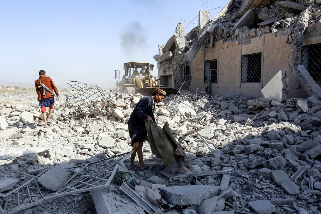 People inspect the rubble of a building hit by an air strike of the Saudi-led coalition south of Sanaa in September 2019 (AFP)