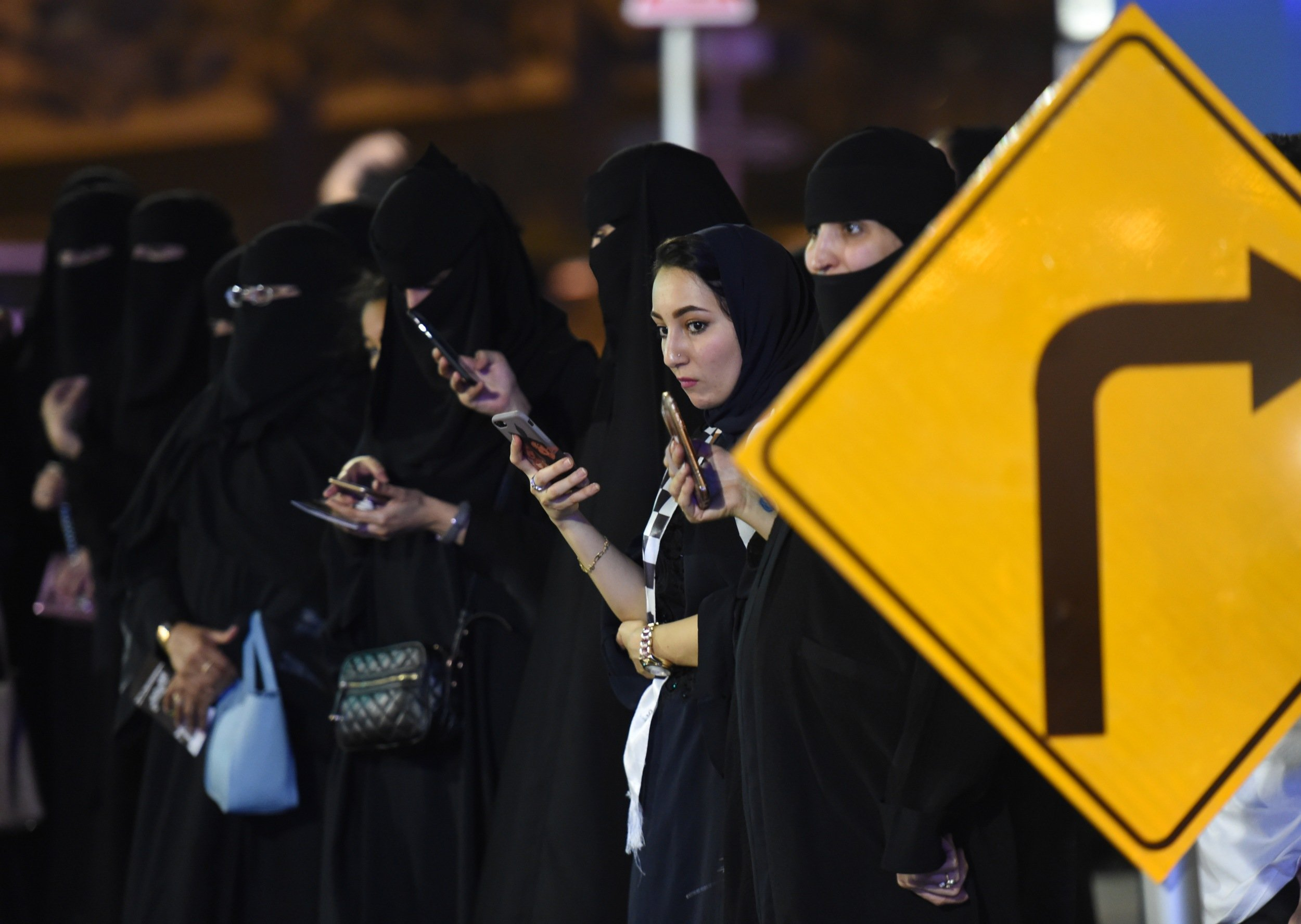 Saudi women look at their phones in the capital Riyadh on 21 June 2018 (AFP)
