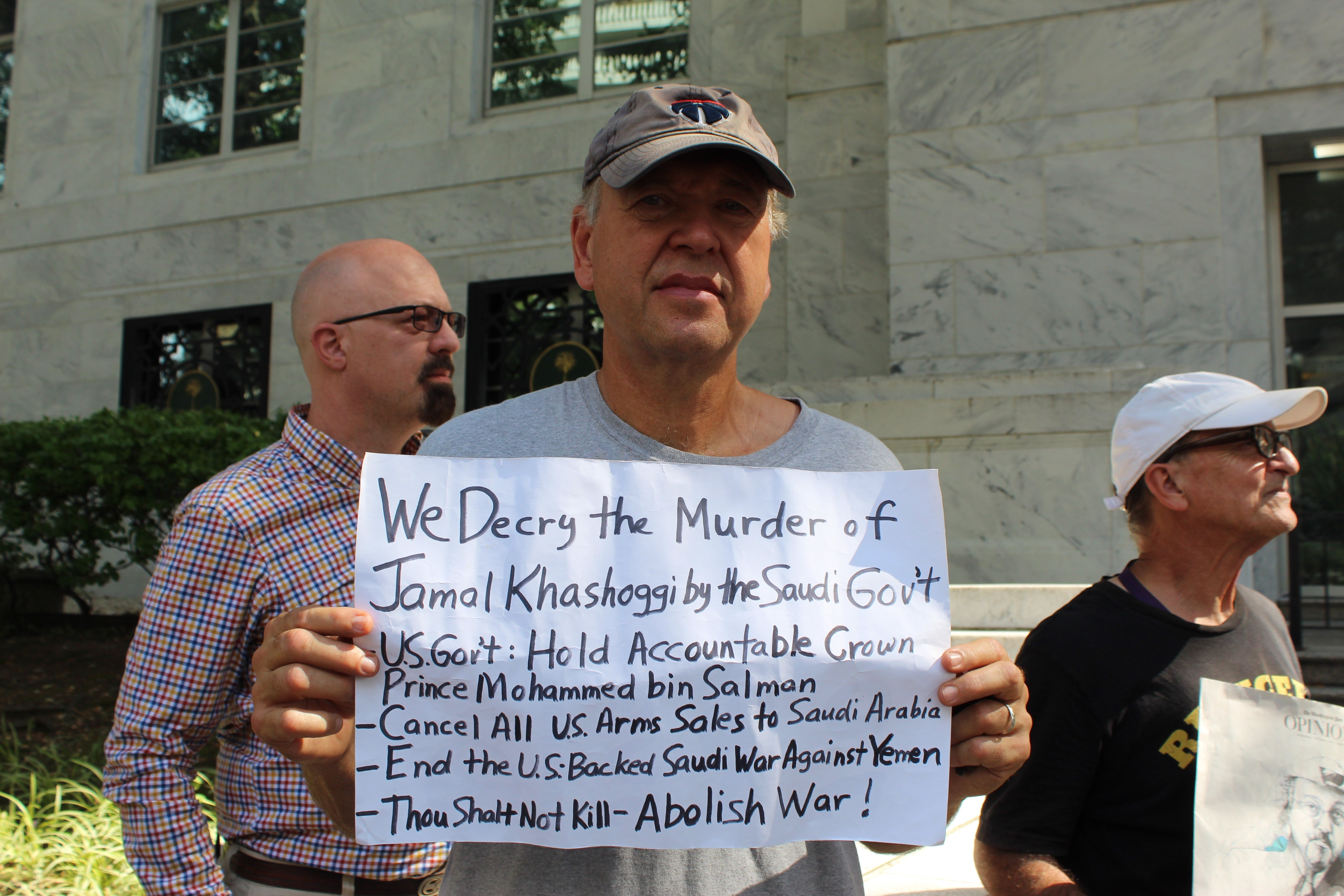Martin Laffin holds a sign, asking the US government to hold Saudi Arabia accountable for the 2018 murder of Jamal Khashoggi on 2 October 2019 (MEE/Sheren Khalel)
