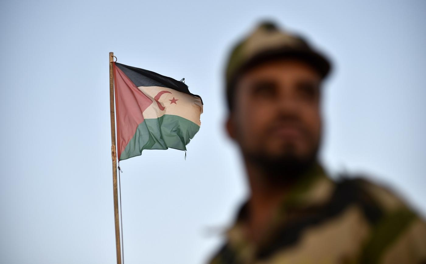 A soldier wearing the Polisario Front uniform stands by a Sahrawi flag in 2017 (AFP)