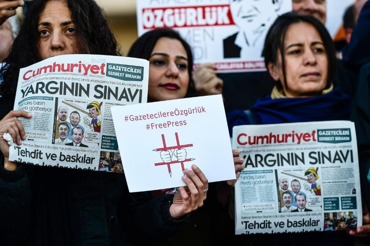 Protesters hold copies of Turkish daily newspaper Cumhuriyet and placards during a demonstration in front of a courthouse in Istanbul on 31 October 2017. (AFP)