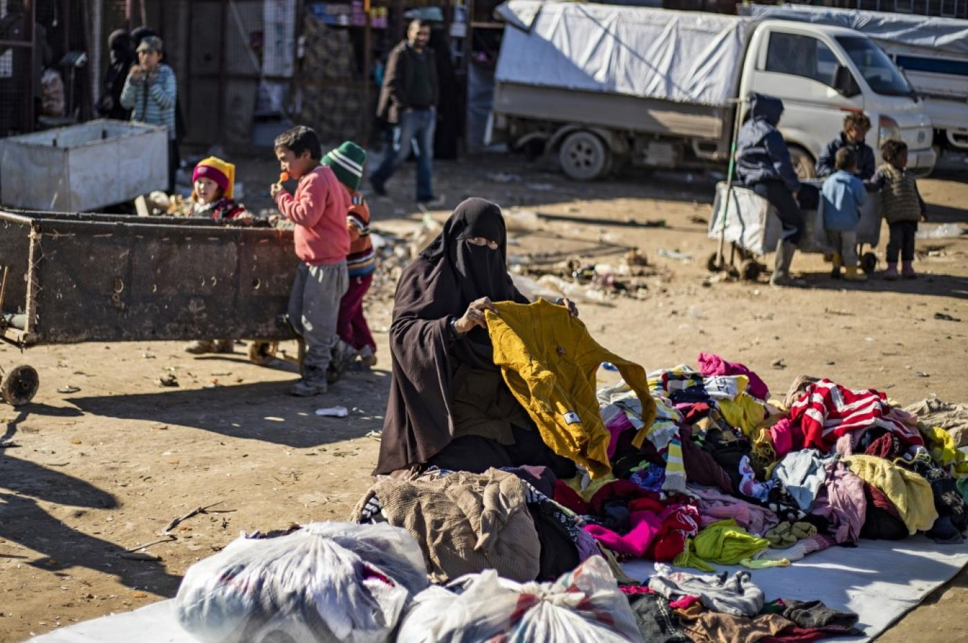 A woman sorts used clothing on the ground at the Kurdish-run al-Hol camp in northeastern Syria on 14 January (AFP/File photo)