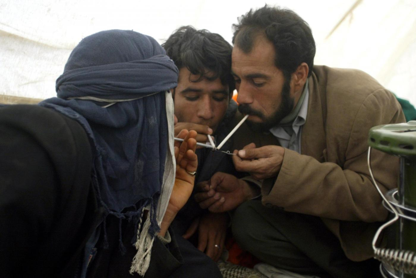 Iranian men smoke opium in a tent in the southeastern Iranian city of Bam on 31 December 2003 (AFP)